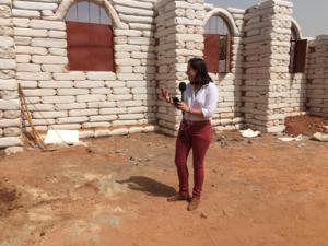 Kerry Alexander next to school made of moon bricks in Senegal